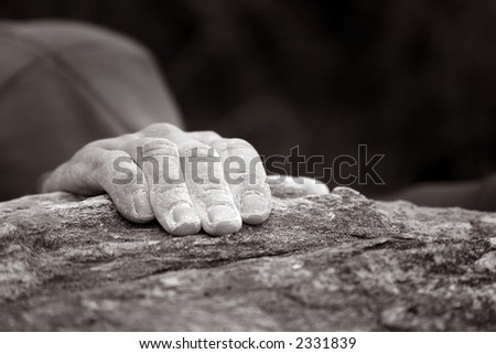 A lonely hand holding onto the top of a rock as a climber reaches the peak. This image has a slight sepia tone to it. - stock photo