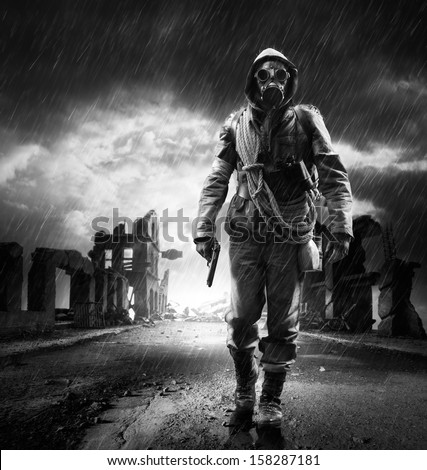 A lonely hero wearing gas mask walking through a city destroyed  - stock photo