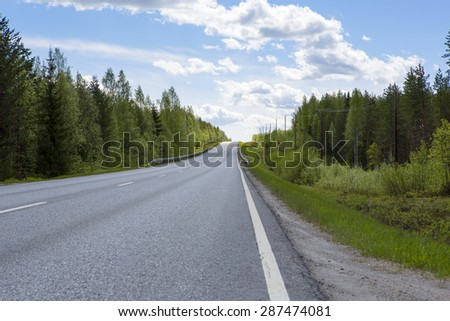 A lonely highway in the Northern part of Finland. - stock photo