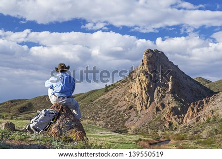 a lonely hiker sitting and contemplating mountain scenery in springtime- Eagle Nest Open Space near Fort Collins, Colorado - stock photo