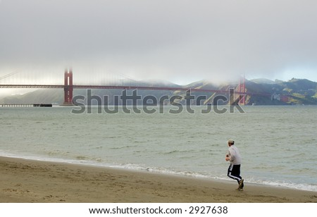 A lonely jogger running towards Golden Gate Bridge on the beach on a cold foggy San Francisco day. Left foot is motion blurred.