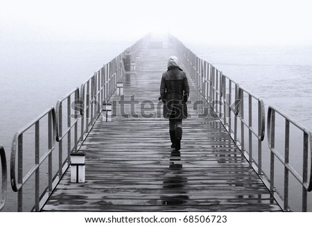 A lonely lady crossing the floating pedestrians' bridge that leads to the islet of Aghios Achilleios in Mikri Prespa lake - stock photo