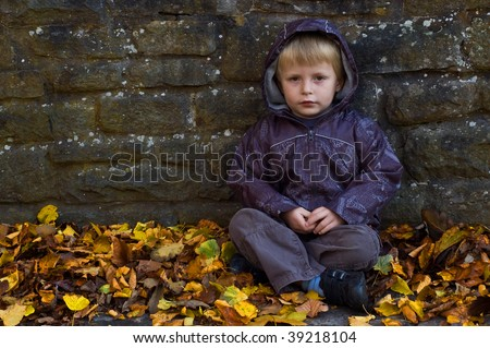 a lonely looking young child sat against a wall with autumn leafs all around him.