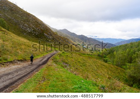 A lonely man walking along a mountain road to the village under a cloudy sky.