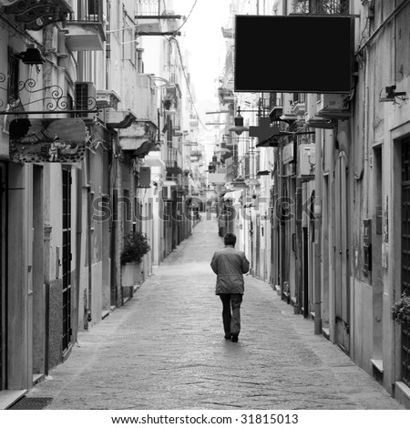 A lonely man walking along a narrow italian medieval street full of closed shops in an early sunday morning - stock photo