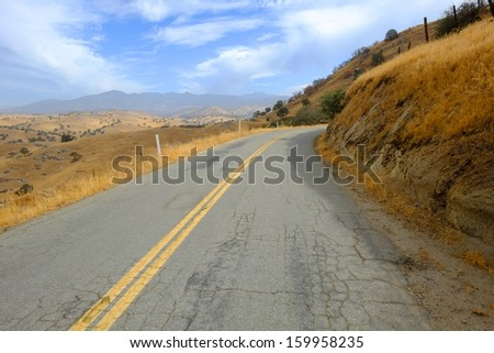 A lonely narrow road winds through the foothills leading to the Southern Sierra Nevada Range in California - stock photo
