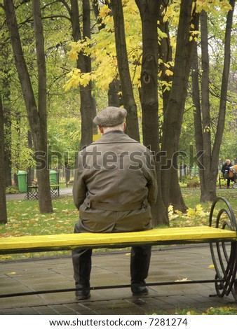 A lonely old man sitting on a bench in a park in Moscow among colorful autumn trees. - stock photo