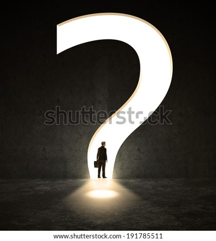 A lonely person walking through a narrow passage in a shape of a question mark - stock photo