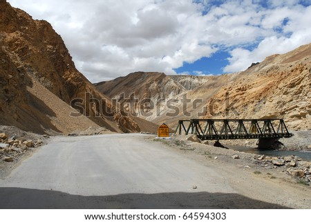a lonely road and a bridge in jammu kashmir ladakh - stock photo