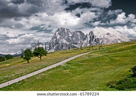 A lonely road in Alpe Di Siusi, in the Italian Alps. - stock photo