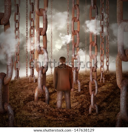 A lonely sad man is chained to the dry landscape with other chains going into the sky for a power or freedom concept. - stock photo