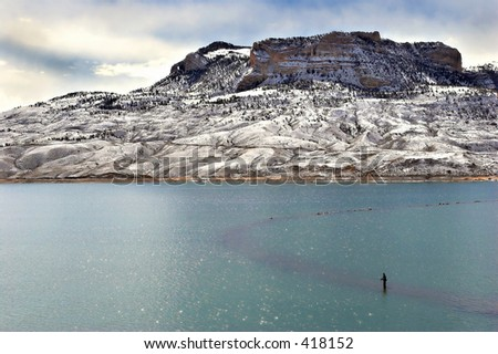 a lonesome fisherman on buffalo bill reservoir, just outside of cody, wyoming - stock photo