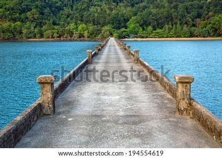A long and small concrete pier on a sea. - stock photo