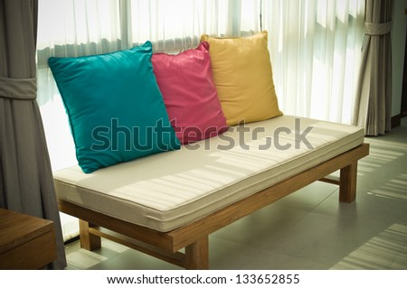 A long chair decorated with three color pillows