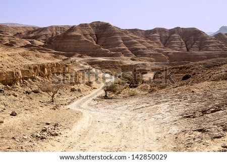 A long dusty road winds through the isolated and remote hills and valleys of the Negev desert. In the background, hills of sedimentary sandstone loom over the road. - stock photo