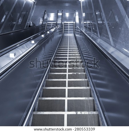 A long escalator leading into an underground passage - stock photo