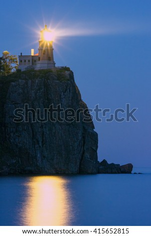 A Long Exposure Late Blue Hour Shot of the Split Rock Lighthouse Casting Light Out Over Lake Superior - stock photo