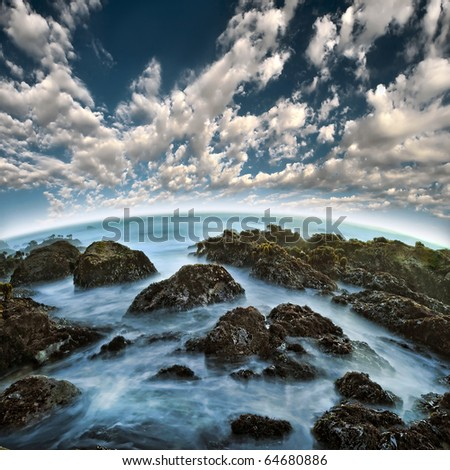 A long exposure of blue water between rocky sea ocean shore at the beach with beautiful clouds above the horizon. - stock photo