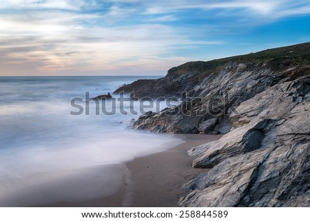 A long exposure of low cliffs and waves at Little Fistral on the Towan Headland at Newquay in Cornwall - stock photo