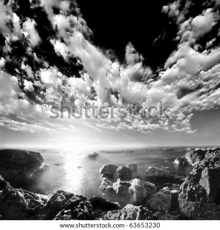 A long exposure of ocean water between sea rocks at the beach with beautiful clouds above the horizon. Black and white infrared photograph - stock photo