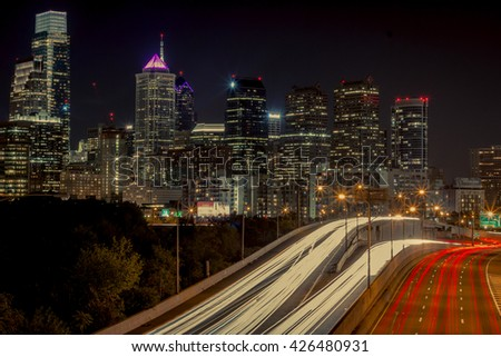 A long exposure of the Philadelphia skyline, with light trails from the freeway below