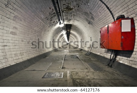 A long foot tunnel under the river Thames to Canary Wharf from Greenwich, London - stock photo