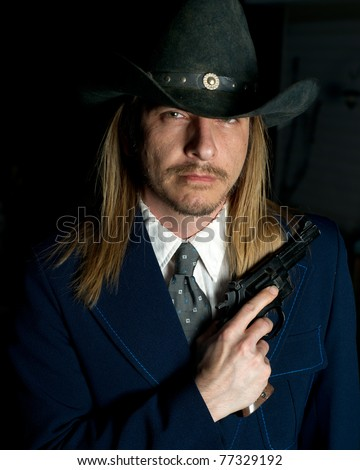 A long haired man in cowboy hat holds a revolver. - stock photo