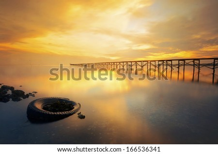 a long jetty and golden light during sunrise - stock photo