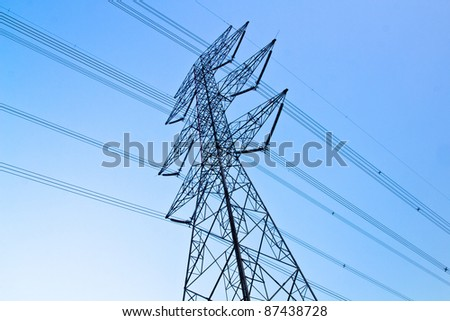 a long line of electrical transmission towers carrying high voltage lines.