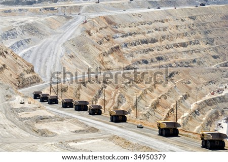 A long line of monster dump trucks drives down into an open pit mine to pick up their next load - stock photo