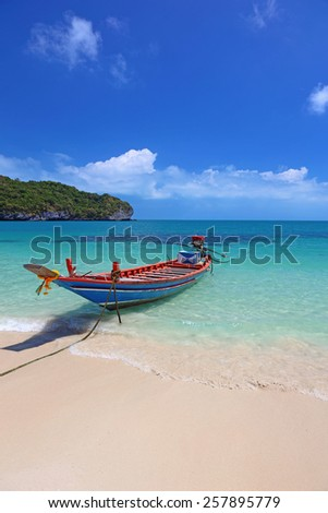 A long nosed boat on the shore of a beautiful tropical island in Thailand.  - stock photo