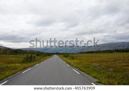 A long, open road surrounded by wild beautiful nature and mountains  - stock photo