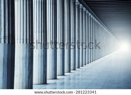 A long passage between many old columns - stock photo