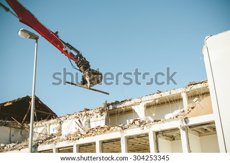 A long-reach excavator pulling apart an old office block. High reach demolition excavator are more often used for tall buildings where explosive demolition is not appropriate or possible - stock photo