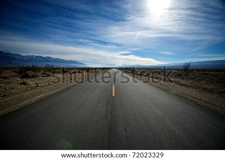 A long straight road runs south from Death Valley into a vast emptiness.