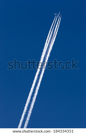 A long trail of jet plane on blue sky - stock photo