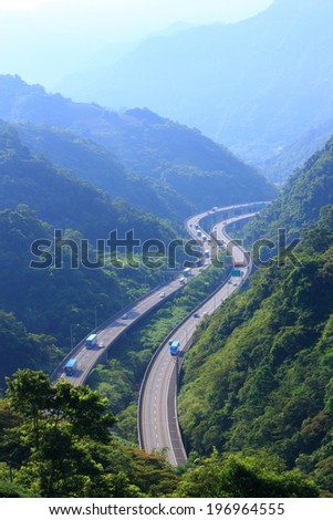 A long winding road travels past the vast hills. - stock photo