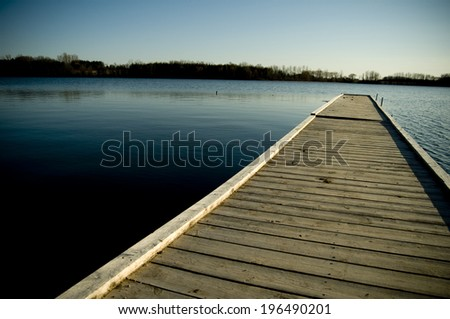 A long wooden dock extending over the water. - stock photo