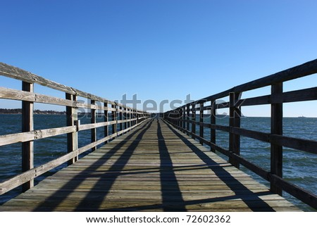 A long wooden fishing pier at the Yorktown beachfront leading out over the York River in Virginia with room for your text. - stock photo