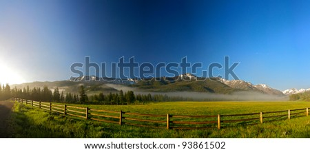 A long wooden rail fence stretches across the front of a Wyoming ranch. - stock photo