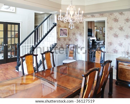 A long wooden table in a modern American luxury home. Six dining room chairs surround the table, and the stairs and foyer are visible in the background. - stock photo
