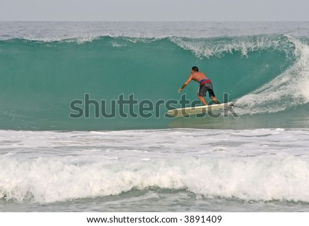 A longboarder rides a clean hollow wave - stock photo
