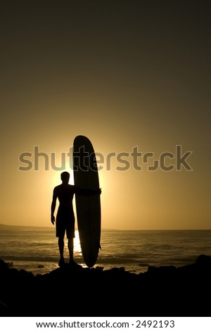 A longboarder watching he waves at sunset in La Santa Lanzarote - stock photo