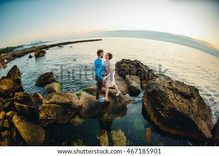 A look from above on the couple standing on the stones in the water