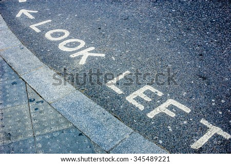 A look left sign written on the asphalt pavement of a road in London England as a warning to tourists of on coming traffic. - stock photo