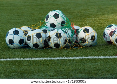 a lot of balls for soccer on a field of artificial grass  for  training  football team - stock photo