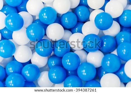 A lot of blue and white plastic balls in playroom.
