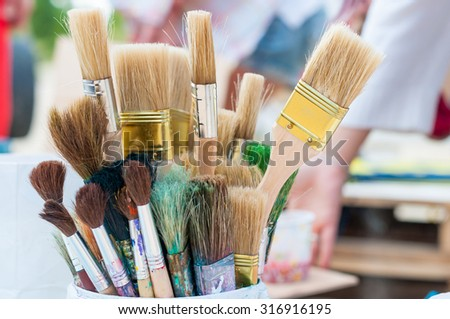 a lot of brushes of different sizes and shapes in soft light and light blur. Artist background - stock photo