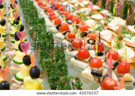a lot of canapes with skewer on buffet table, shallow DOF - stock photo