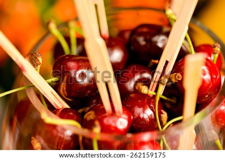A lot of cherries with toothpicks stuck in a glass bowl - stock photo